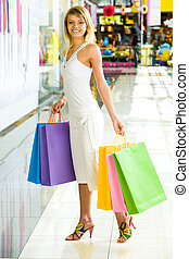 Shopaholic - Beautiful smiling woman standing in the centre...