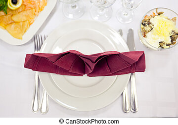 Place setting in red and white tones. Vertical perspective.
