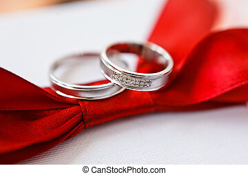 gold wedding rings on red