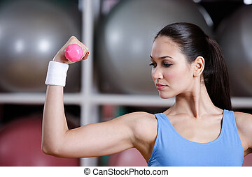 Young woman training with pink dumbbells - Young woman works...