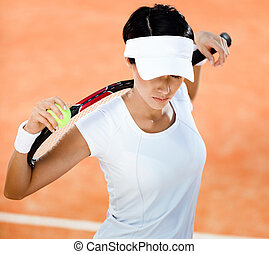 Woman keeps tennis racket and ball on her shoulders - Woman...