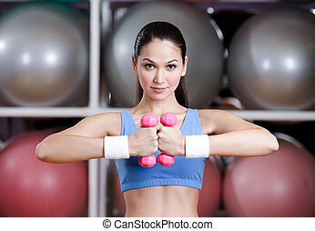 Young woman in sportswear training with dumbbells