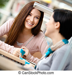Two girls communicate sitting at the desk