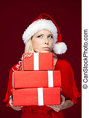 Woman in Christmas cap hands a set of presents
