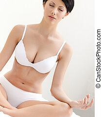 Woman meditates sitting on the bed, white background