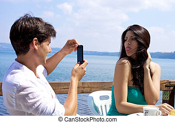 Man taking picture of beautiful wife on italian lake