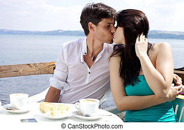 Beautiful woman kissing boyfriend during breakfast in front of a lake