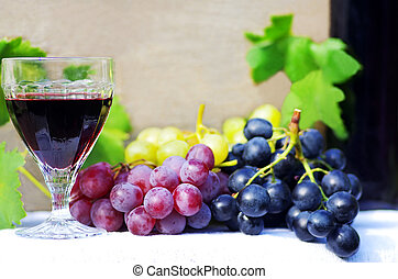 glass of red wine with grapes on a table
