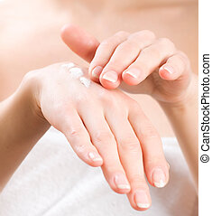 Female applying moisturizer to her Hands after bath Skincare...