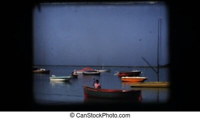 Vintage 8mm. Docked boats in a calm bay in southern Italy