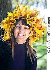 Laughing woman wearing autumn leaves