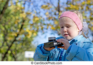 Small girl intrigued by an old camera