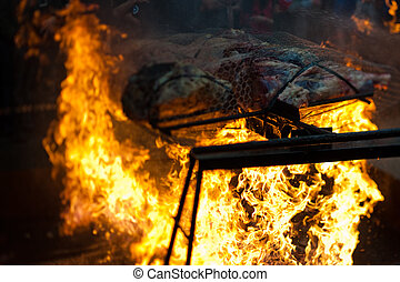 Beef roasting on a spit over a bonfire