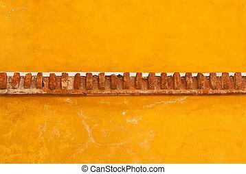 Yellow adobe wall with brick trim