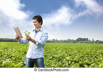 asian farmer with tablet pc