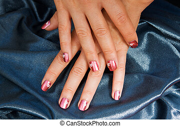 Woman manicure arranged with blue satin