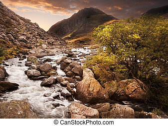 Dramatic sunset with beautiful sky over mountain range giving a strong moody landscape wiht flowing waterfall in foreground