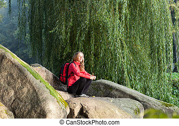 Hiker woman sitting on a halt in rocks among the green nature