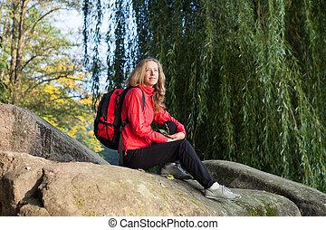 Woman backpacker enjoying relaxation on a halt in rocks