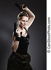 Sexy woman holding gun on gray