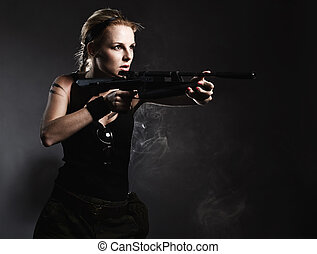 Sexy woman with rifle on dark
