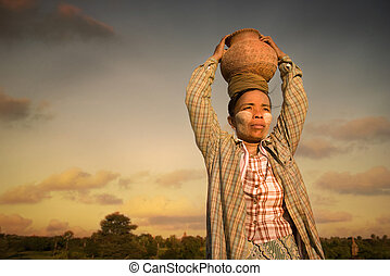 traditional myanmar farmer carrying pot on her head during...