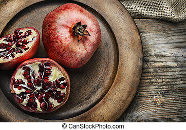 Pomegranate in rustic wooden plate