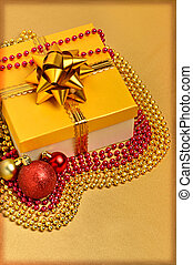 Yellow gift box with christmas baubles and beads around
