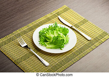 diet concept. green lettuce on a plate with a fork and knife