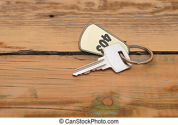 silver key with golden label on wood background