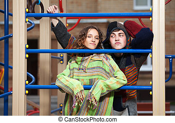 Young hippie couple on the children playground