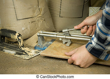 tiler using tile cutter on floor with tools and materials