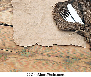 A place setting with silver fork and knife on old sacking...