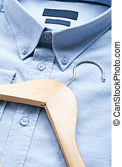 Shirt and cloth hanger - Wooden cloth hanger on top of blue...