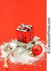 Christmas sleigh with gift on red background