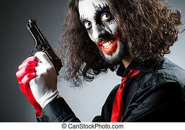 Evil clown with gun in dark room