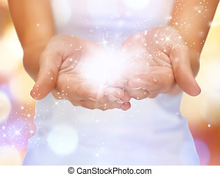 magic twinkles on female hands - bright closeup picture of...