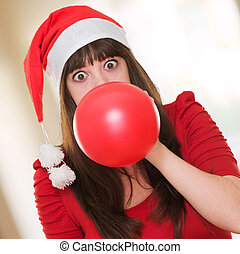 woman blowing balloon and wearing a christmas hat against an...