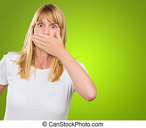 Young Woman With Hand On Mouth against a green background