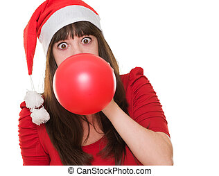 woman blowing balloon and wearing a christmas hat against a...