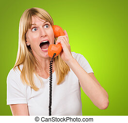 shocked woman talking on telephone against a green...