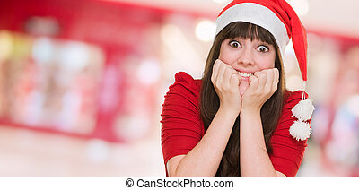 Extremely excited woman wearing a christmas hat at a mall,...
