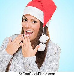 Excited woman wearing a christmas hat against a blue...