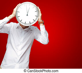 Young Man Holding Big Clock Covering His Face On Red...
