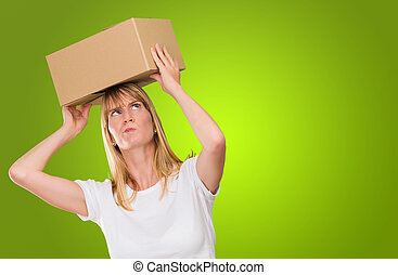 woman holding a box on her head against a green background