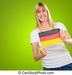 woman holding a german flag against a green background