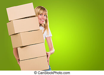 woman holding a pile of boxes against a green background