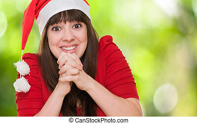 excited woman wearing a christmas hat against a nature...
