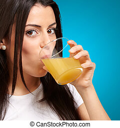 Women Drinking Orange Juice On Blue Background