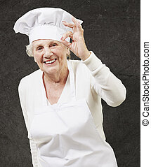 senior woman cook doing an excellent symbol against a grunge...